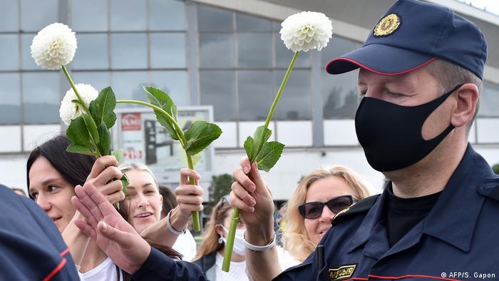 Mulheres abraçam policiais e colocam flores em seus equipamentos de proteção