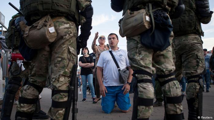 Безоружный демонстрант стоит на коленях перед вооруженным ОМОНом