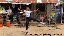 3.7.2020, Lagos, Nigeria, A student of the Leap of Dance Academy, Anthony Madu (L), performs a ballet dance routine in front of his mother's shop in Okelola street in Ajangbadi, Lagos, on July 3, 2020. - The Leap of Dance Academy is a ballet school in a poor district of sprawling megacity of Lagos that aims to bring classical dance to underprivileged children in Africa's most populous nation. The school is the brainchild of self-taught ballet lover Daniel Ajala, who opened its doors in late 2017 after studying the dance moves online and in books. Now the academy, which Ajala funds out of his own pocket, has 12 pupils aged from 6 to 15. The lessons are free and shoes and kit provided to the children, most of whom had never heard of ballet before they got involved. (Photo by Benson Ibeabuchi / AFP) (Photo by BENSON IBEABUCHI/AFP via Getty Images)