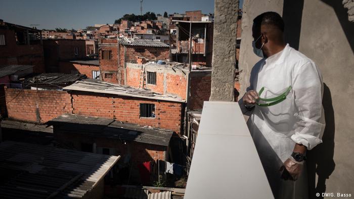 Homem de máscara observa favela de Paraisópolis, em São Paulo