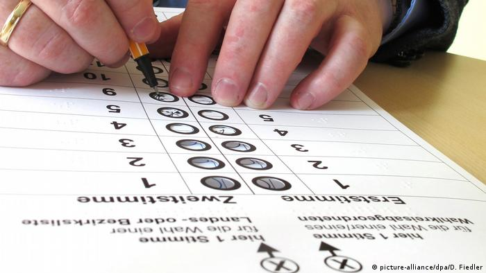 A blind person fills out their ballot