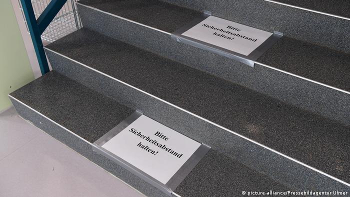 На ступеньках школьной лестницы надпись: Пожалуйста, соблюдайте безопасную дистанцию!