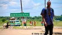 A man walks by the main entrance to the city on March 8, 2018 in Mocimboa da Praia, Mozambique. Security is increased in the area following a two days attack from suspected islamists in October last year where they took control of the city. / AFP PHOTO / ADRIEN BARBIER (Photo credit should read ADRIEN BARBIER/AFP via Getty Images)