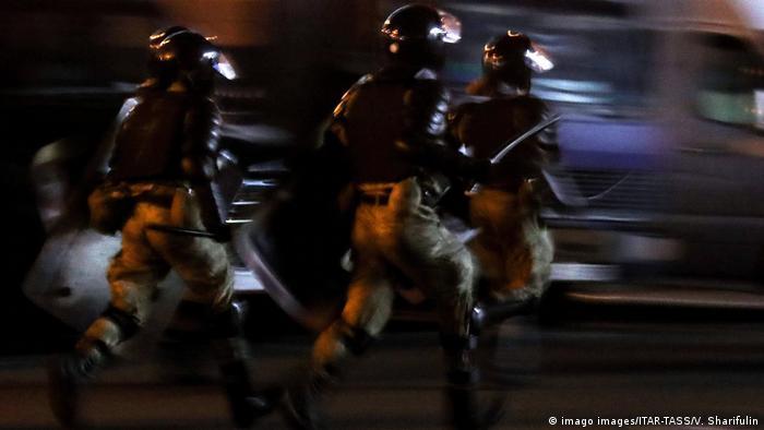 Силовики бегут по улице во время разгона протестов в Минске