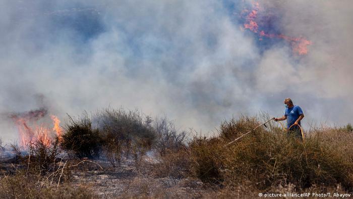 Un trabajador israelí de la Autoridad de Naturaleza y Parques intenta extinguir el fuego causado por un globo incendiario lanzado por los palestinos desde la Franja de Gaza, en el lado israelí de la frontera entre Israel y Gaza, cerca del kibutz Or HaNer, el miércoles 12.08.2020
