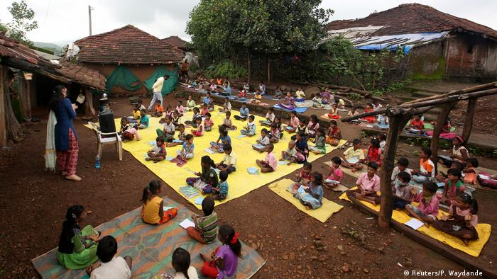 Children, who have missed their online classes due to a lack of internet facilities, maintain a safe distance as they listen to prerecorded lessons (Reuters/P. Waydande )