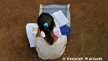 A girl, who has missed her online classes due to a lack of internet facilities, sits on the ground in a circle drawn with chalk to maintain safe distance as she listens to pre-recorded lessons over loudspeakers, after schools were closed following the coronavirus disease (COVID-19) outbreak, in Dandwal village in the western state of Maharashtra, India, July 23, 2020. Picture taken July 23, 2020. REUTERS/Prashant Waydande