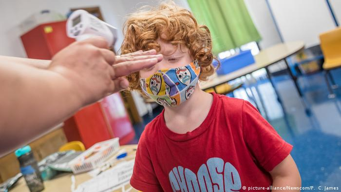 A young boy in a mask has his temperature checked at school (picture-alliance/Newscom/P. C. James)