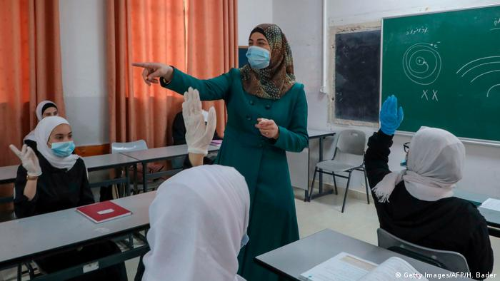 A Palestinian teacher addresses high school students in a mask (Getty Images/AFP/H. Bader)
