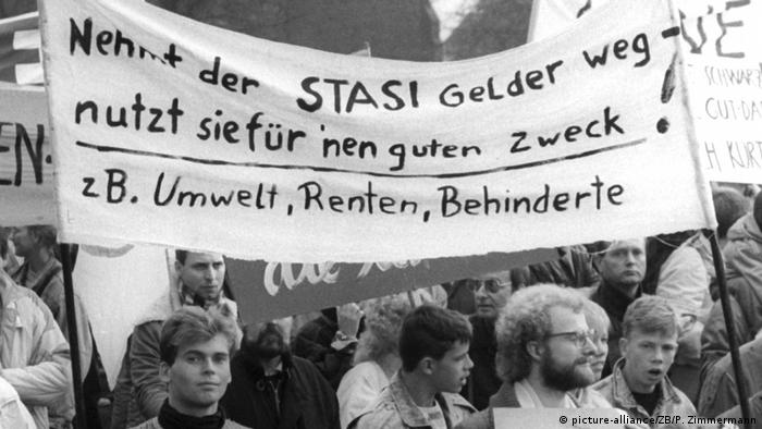 Black and white photo of an East Berlin demonstration with a banner calling for defunding of the Stasi and more investment in environment, pension plans and the disabled