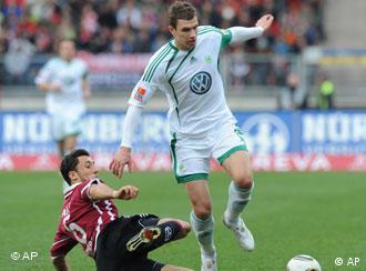 Edin Dzeko vom VfL Wolfsburg setzt sich gegen einen Nürnberger Abwehrspieler durch. (Foto: AP Photo/Martin Meissner)