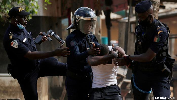 Ivorian riot police arrest a protester
