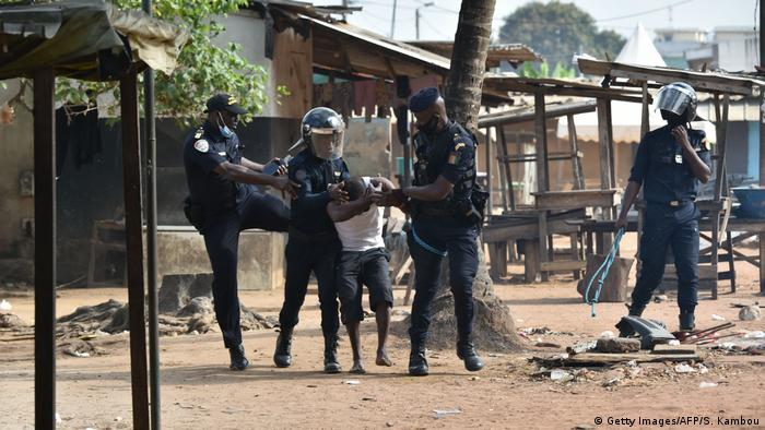 Yopougon municipal police officers arrest a man during a protest against the third term of Ivory Coast President Alassane Ouattara in the Yopougon area of Abidjan