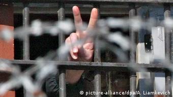 Рука с изображением V протянута из-за решетки тюрьмы
