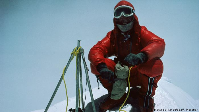 Bergsteiger Reinhold Messner hockt auf dem Gipfel des Mount Everest