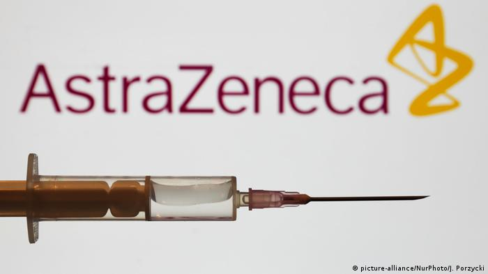 Seringa diante de logo da farmacêutica AstraZeneca