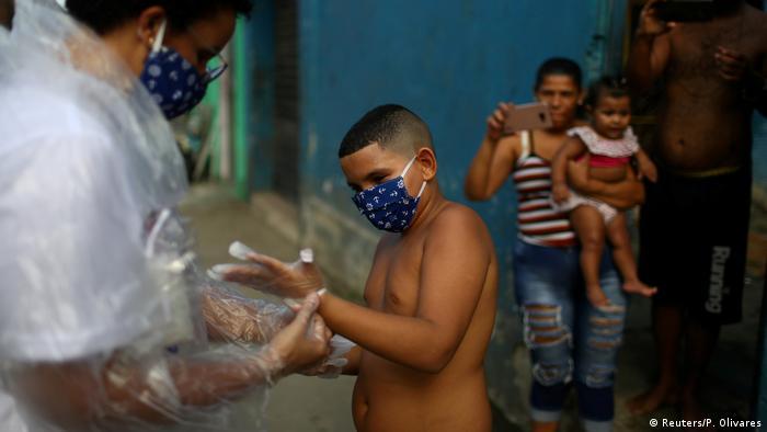 Teacher Maura Silva helps her student Yuri Araujo Silva put on gloves (Reuters/P. Olivares)