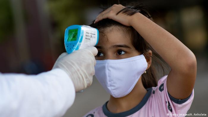 Funcionário mede temperatura de criança em escola em Brasília