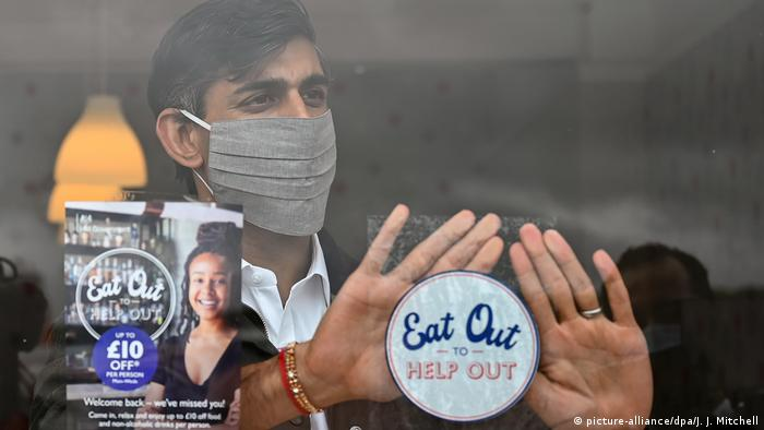 Rishi Sunak behind window displaying eat out to help out sticker (picture-alliance/dpa/J. J. Mitchell)