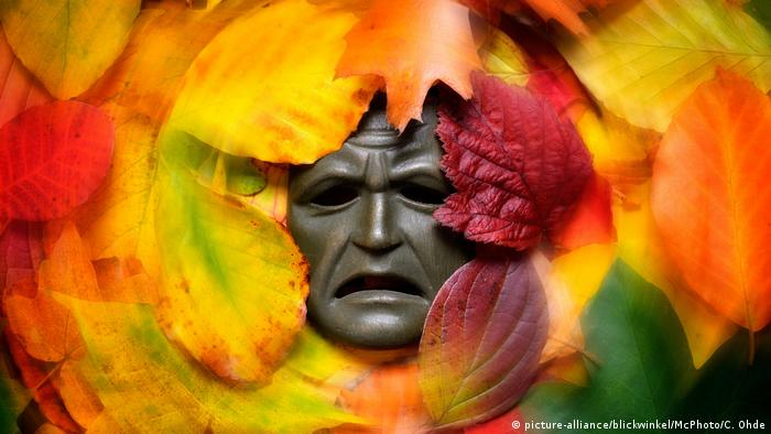 gambar simbol menunjukkan topeng di antara daun warna-warni