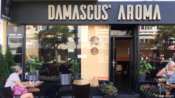 Mesas com pessoas sentadas diante de uma parede de vidro com os dizeres Damascus Aroma