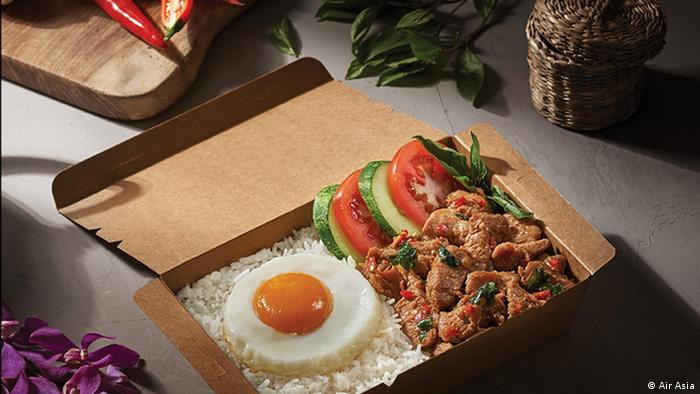 A picture of a meal consisting of rice, meat, vegetables and afried egg, and served by Air Asia