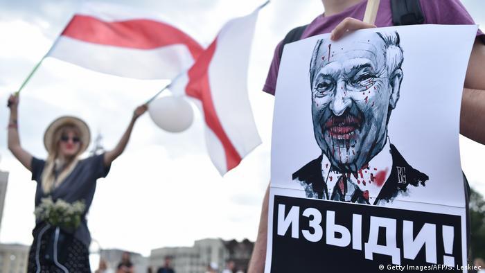 Cartaz com retrato de presidente Alexander Lukashenko e dizeres Dá o fora! em bielorrusso. Ao fundo, manifestante agita bandeira vermelho-e-branca