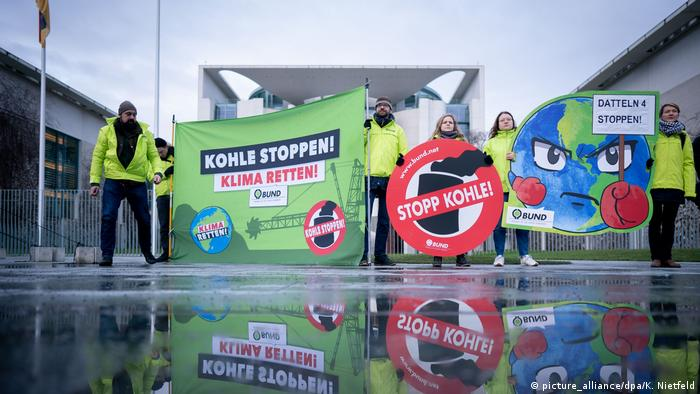 Activists with posters reading 'save the climate' and 'stop coal energy'