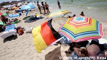 Spanien | Deutsche Touristen mit deutscher Fahne am Strand