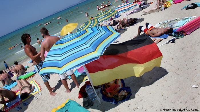 Spanien | Deutsche Touristen mit deutscher Fahne am Strand (Getty Images/AFP/J. Reina)