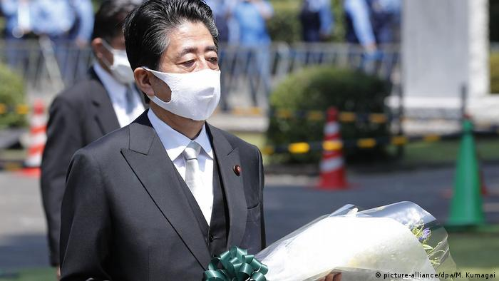 Shinzo Abe, de máscara, carrega flores no Cemitério Nacional de Chidorigafuchi, em Tóquio