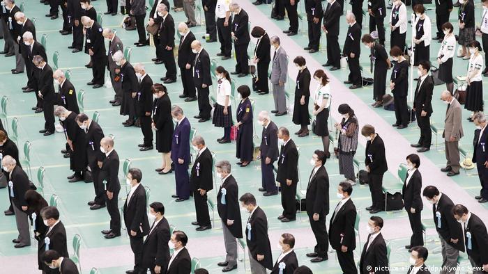 Pessoas de máscara, enfileiradas e em pé, durante cerimônia pelos 75 anos da rendição japonesa na Segunda Guerra