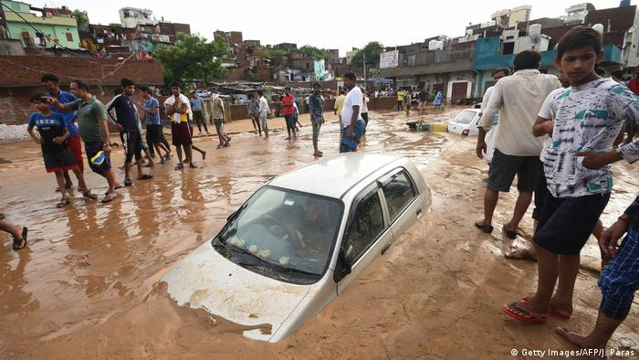 A car partially covered in mud after monsoon rains