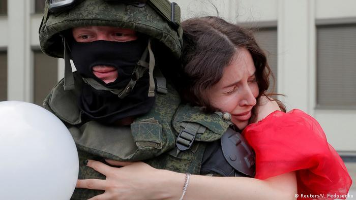 Belarus - Demonstrantin in rotem Kleid umarmt einen Polizisten