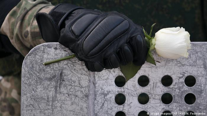 Gloved hand of a Belarusian law enforcement officer holding white rose