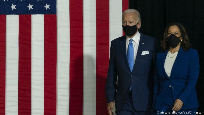Joe Biden e Kamala Harris de máscara diante de bandeira dos EUA