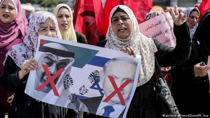 Palästinensiche Frauen halten Anti-Israel-Plakate und Plakate gegen die Vereinigten Arabischen Emirate hoch