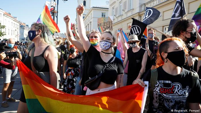 Pro-LGBT+ protesters gesture in a standoff with nationalists in Warsaw