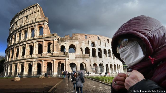Людина в захисній масці на тлі Колізею в Римі (фото з архіву)