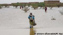 KHARTOUM, SUDAN - AUGUST 03: A woman wades through a submerged field after floods brought by the strong rains that were effective last week in the southeast of Khartoum, the capital of Sudan, continue to affect life negatively on August 03, 2020. Mahmoud Hjaj / Anadolu Agency | Keine Weitergabe an Wiederverkäufer.
