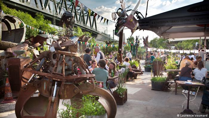 People sitting at tables among metal sculptures at the beer garden Odonien, Cologne (Laurence Voumard)