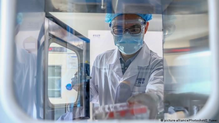 चीन के बीजिंग में स्थित एक वैक्सीन उत्पादन इकाई में वैक्सीन सैंपल के साथ एक रिसर्चर.
