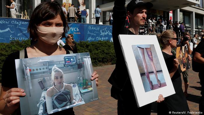 Люди держат фотографии избитых в СИЗО