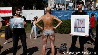 Люди, задержанные в ходе протестов в Беларуси, демонстрируют побои