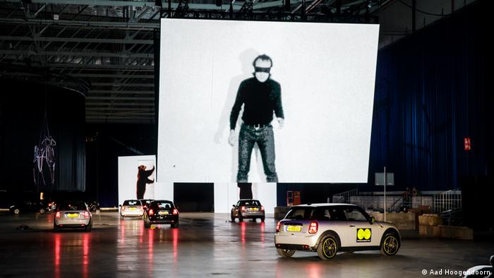 Large screens with the image of a man standing in a mask loom above cars driving through the exhibition hall.