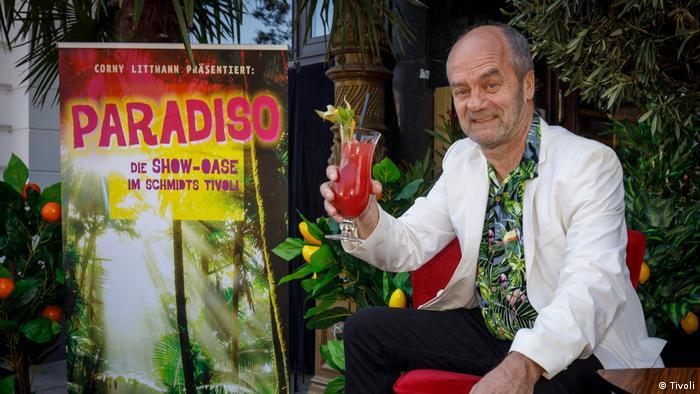 Corny Litmann nazdravlja pred plakatom za svoju predstavu