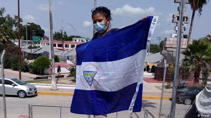 Refugiada de máscara segura a bandeira da Nicarágua