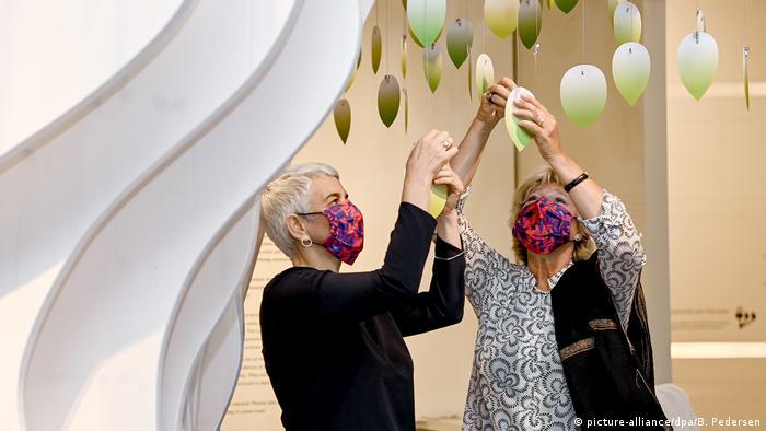 Mulheres de máscaras penduram folhas de papel em instalação do Museu Judaico de Berlim