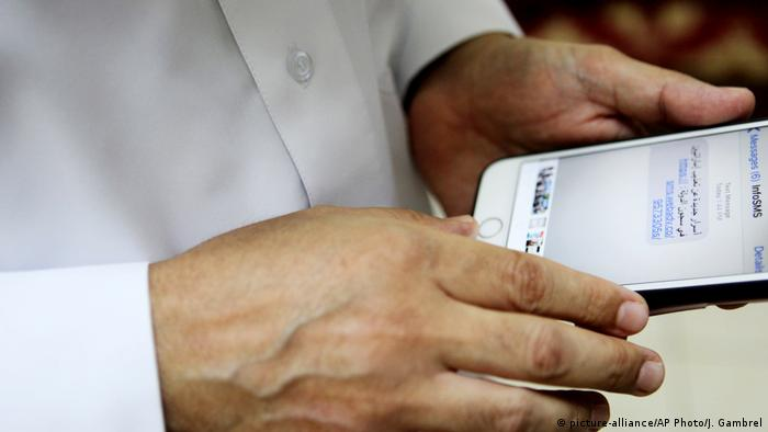 Human rights activist Ahmed Mansoor showing a screenshot of spoof messages on his phone