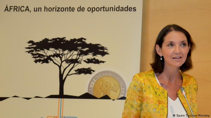 Picture of Reyes Maroto as she presents her Horizonte Africa plan in front of a poster that shows an African landscape